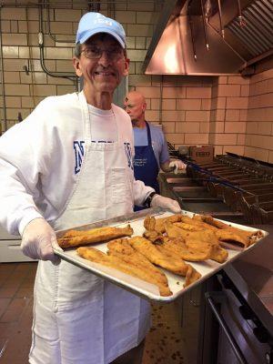 A parishioner holding a tray of breaded fish.