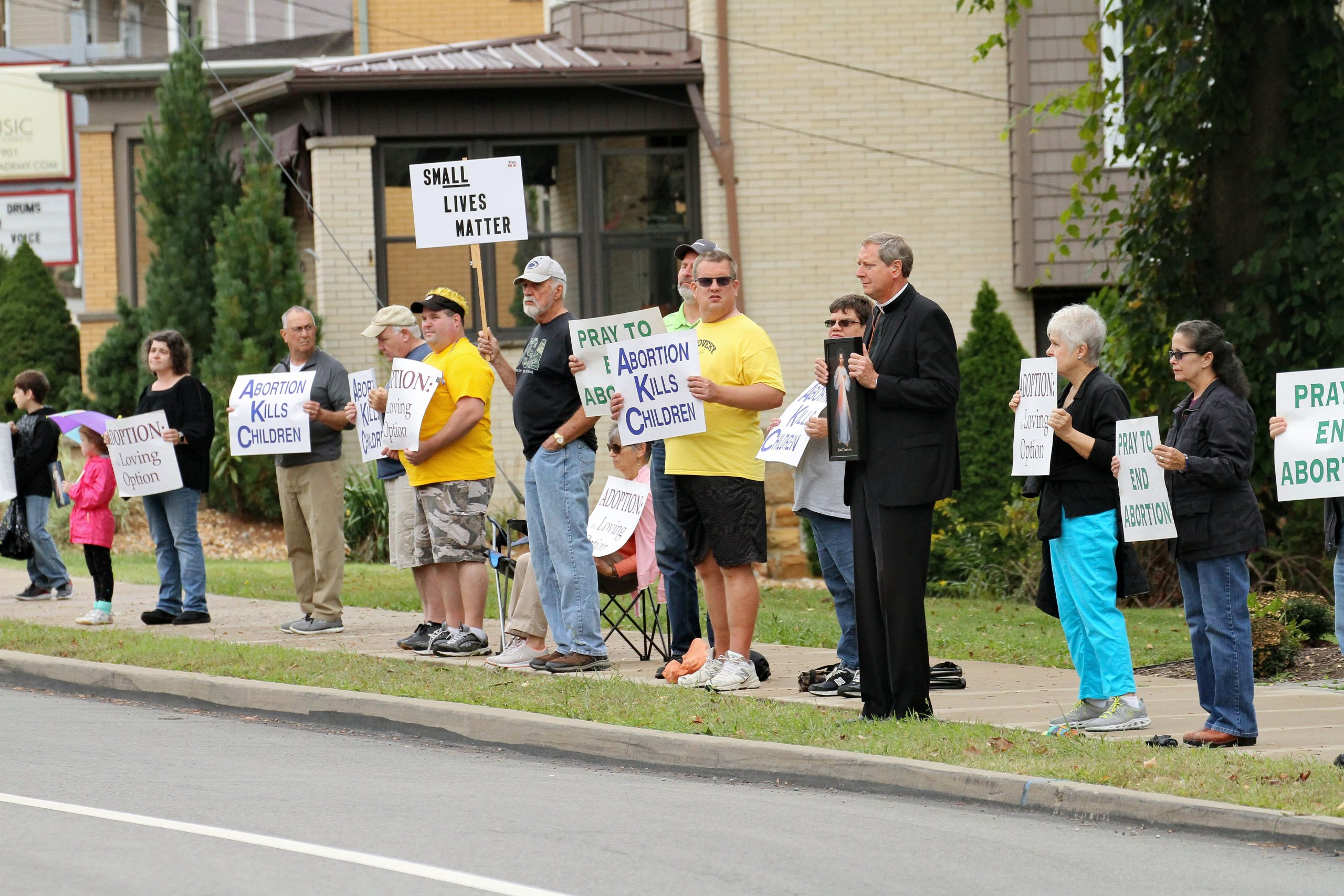 A group of parishioners stand along the side of the road holding signs.